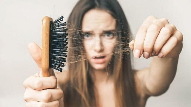 woman shocked to see hair falling out in brush